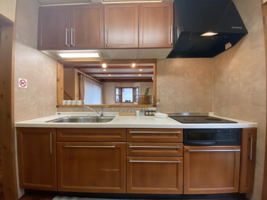 キッチンはIHクッキングヒーター。正面は対面キッチンです。右手には勝手口があり屋根付きの裏庭に続きます。