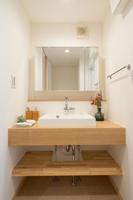 木の造作洗面化粧台。洗面化粧台下のオープンスペースに体重計を置いたりカゴを置いたりできます。(内装)